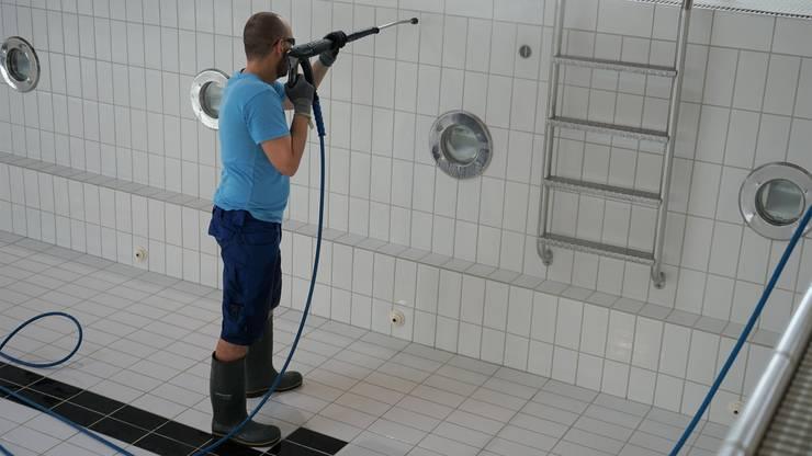 Jede Kachel des Schwimmbeckens wird mit einem Hochdruckreiniger von Schmutz befreit.