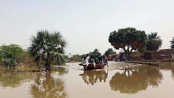 Bei Überschwemmungen wegen heftigen Regenfällen im Sudan sind seit Anfang Juli mindestens 62 Menschen gestorben. In einer Regenpause kehren Einwohner von Wad Ramli in ihre Häuser zurück, um einen Teil ihrer Habseligkeiten in Sicherheit zu bringen.