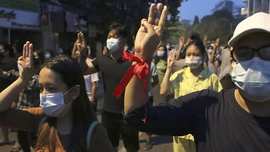 Mehrere Demonstranten heben ihre Hand zum Dreifingergruß während einer Kundgebung in Yangon. Foto: Uncredited/AP/dpa