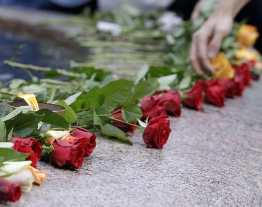 Menschen legen Rosen neben einen Brunnen