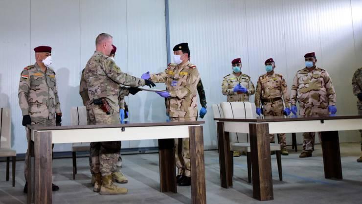 US-Brigadegeneral Vincent Barker (2. links) gibt einem irakischen General bei der Übergabe der Basis K1 an den Irak die Hand. Die von den USA geführte Militärkoalition zog sich am Sonntag von der dritten Basis im Irak zurück.