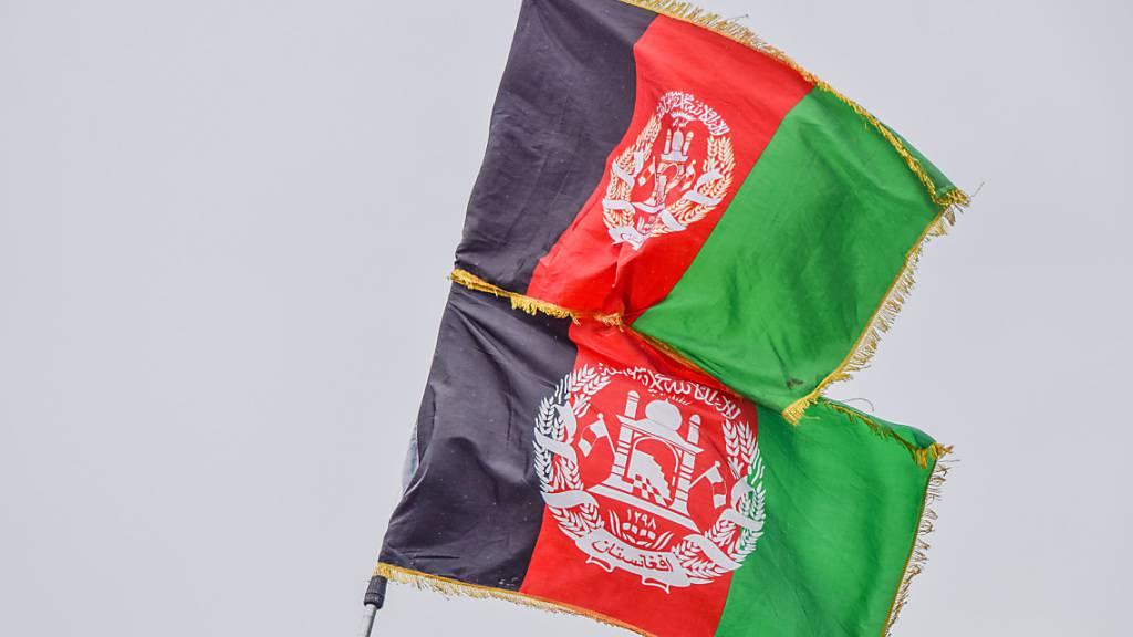Demonstranten gegen die Taliban zeigen die afghanische Flagge. Foto: Vuk Valcic/SOPA Images via ZUMA Press Wire/dpa