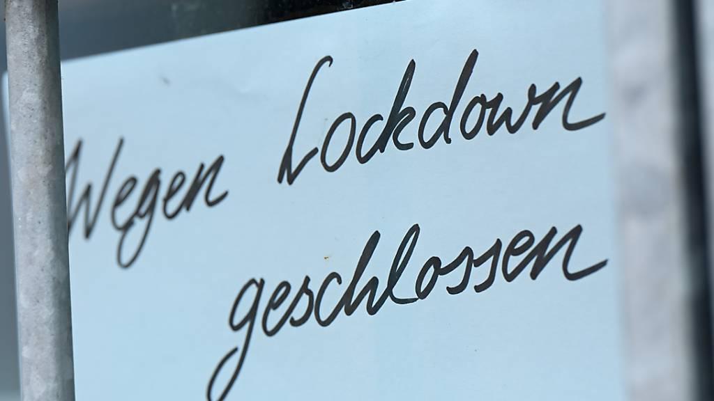 Ein Zettel mit der Aufschrift «Wegen Corona geschlossen» hängt am Schaufenster eines Geschäfts.