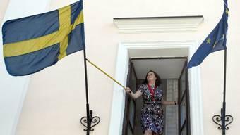 Eine Angestellte der schwedischen Botschaft in Minsk richtet die schwedische Flagge (Archiv)