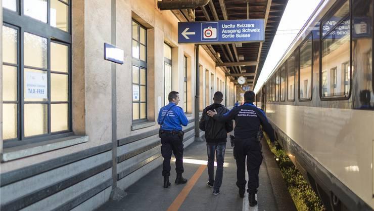 Grenzwächter bringen in Chiasso einen Asylbewerber zur Personenkontrolle.key