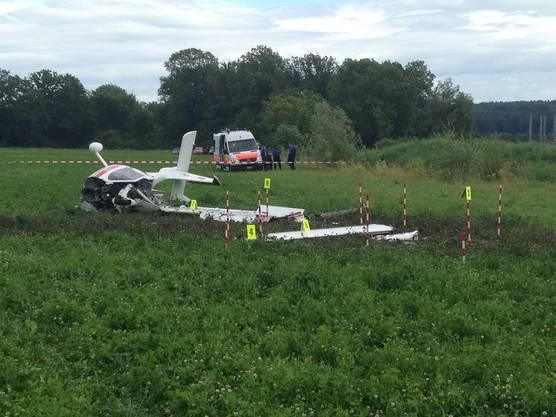Das Flugzeug liegt auf der linken Seite im Gras, ein der Tragflächen ist abgebrochen.