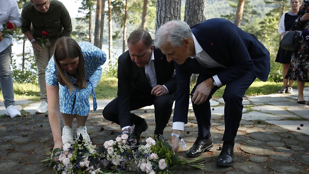 Astrid Hoem, Vorsitzende der AUF,  Stefan Löfven, Ministerpräsident von Schweden, und Jonas Gahr Støre, Vorsitzender der norwegischen Arbeiterpartei, legen Blumen nieder. Foto: Beate Oma Dahle/NTB/dpa