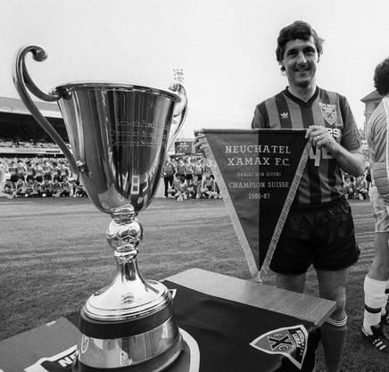 Zweimal wird Xamax Schweizer Meister. Hier präsentiert der legendäre irische Stürmer Don Givens 1987 neben den Meisterkübel den Wimpel, der das bezeugt.