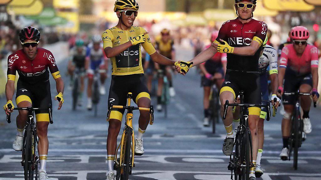 Egan Bernal in Gelb und sein Teamkollege und Vorjahressieger Geraint Thomas (rechts) überqueren die Ziellinie in Paris