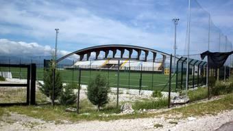Ein Stadium wartet auf Spieler und Zuschauer, doch rund herum sind nur Olivenbäume.