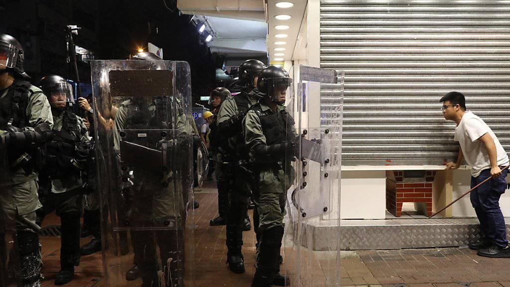 Ein Mann schliesst in Hongkong sein Geschäft, weil er Ausschreitungen und Sachbeschädigungen befürchtet.