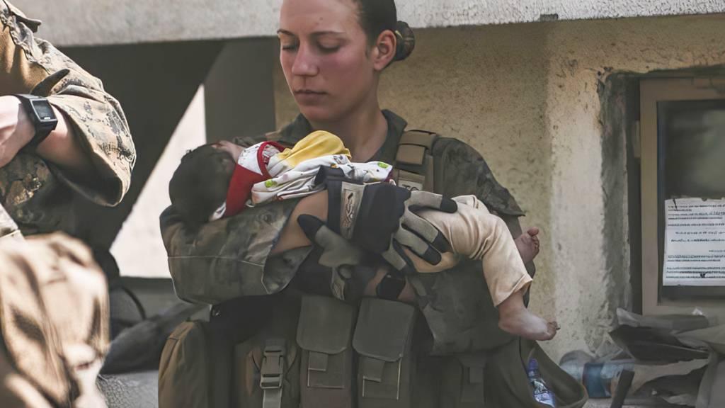Die Unteroffizierin Nicole Gee vom US Marine Corps beruhigt ein Kleinkind am Flughafen in Kabul. Tage danach stirbt sie bei einem Terroranschag. Foto: Sgt. Isaiah Campbell/U.S. Marine Corps via AP/dpa - ACHTUNG: Nur zur redaktionellen Verwendung und nur mit vollständiger Nennung des vorstehenden Credits