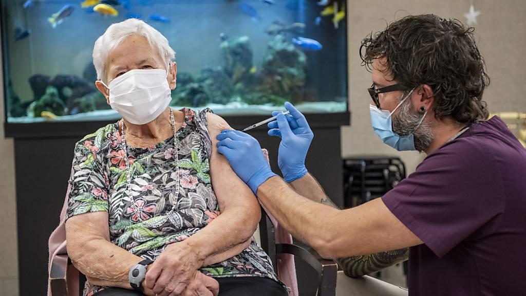 In einem Luzerner Pflegeheim lässt sich eine Frau gegen das Coronavirus impfen.