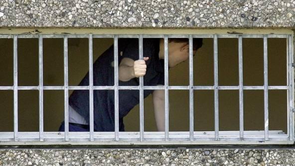 Ein Gefangener hinter Gitterstäben (Symbolbild)