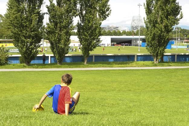 Der FCB-Fan schaut das Spiel vom Rasen neben dem FCB-Campus.