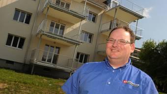 Felix Grendelmeier lächelt, doch er scheint Angst vor den Asylsuchenden zu haben, die in den Wohnungen in seinem Rücken einziehen werden.