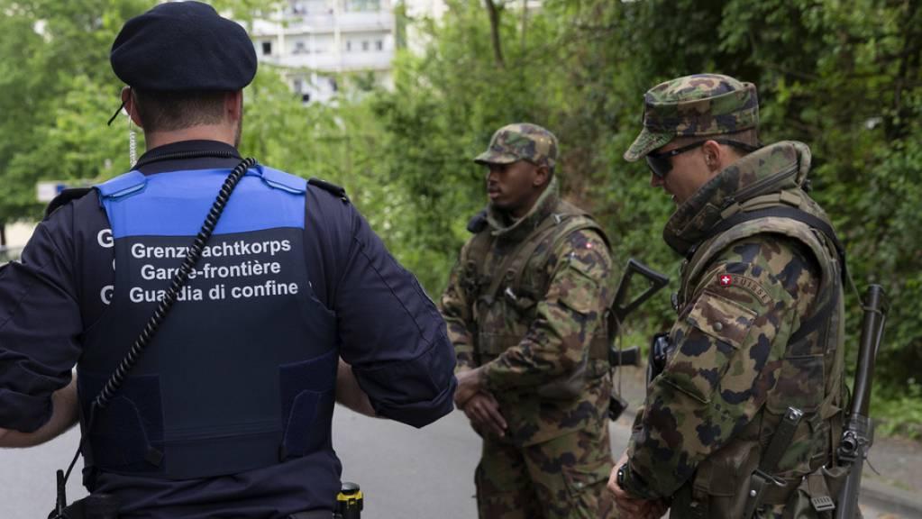 Ein Schweizer Grenzbeamter und Soldaten sichern die Grenze bei Thonex vor Corona-Sündern. Künftig - so will es das revidierte Zollgesetz - könnten auch Handelswarenzollbeamte mit Waffen aufgerüstet werden. Das stösst den meisten, die sich zum Gesetzesentwurf vernehmen lassen, sauer auf. (Symbolbild)