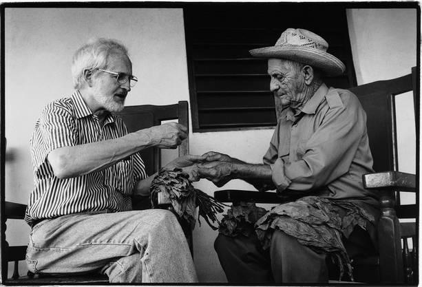 Heinrich Villiger prüft mit einem kubanischen Bauern die Qualität von Tabakblättern.