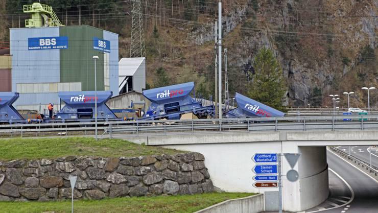 Einer der Kieswaggons hängt gefährlich nah über dem Autobahnzubringer.