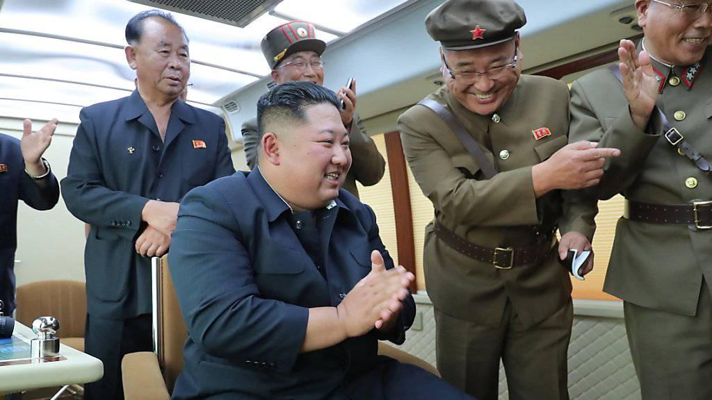 Nordkoreas Machthaber Kim Jong Un beim jüngsten Raketentest mit Militärs an einem unbekannten Ort.