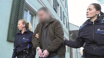 In Handschellen wird der Angeklagte von zwei Polizistinnen in Dornach zum Prozess geführt.