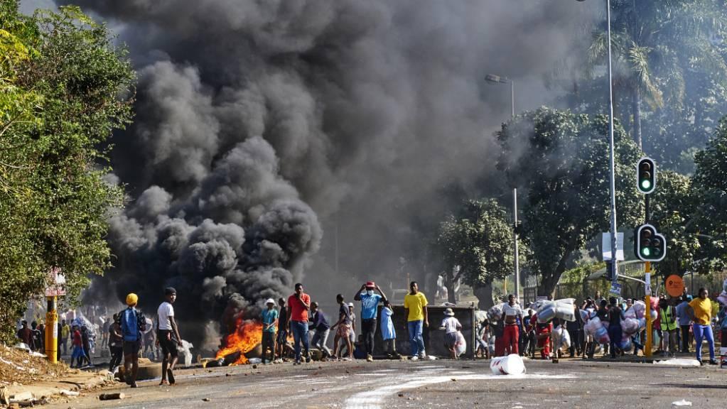 dpatopbilder - Plünderer stehen vor einem Einkaufszentrum neben einer brennenden Barrikade in Durban. Nach mehreren Tagen der gewalttätigen Proteste und Plünderungen formiert sich in einigen Provinzen Südafrikas ziviler Widerstand. Foto: Andre Swart/AP/dpa