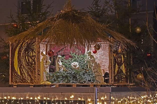 Jesus im Tannengrün Auf einem Garagendach in Wolfwil wurde diese Krippe aufgestellt. Die weissen Figuren sind um ein Bett aus Tannenästen angeordnet.