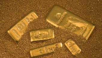 Goldbarren in Goldstaub (Symbolbild).