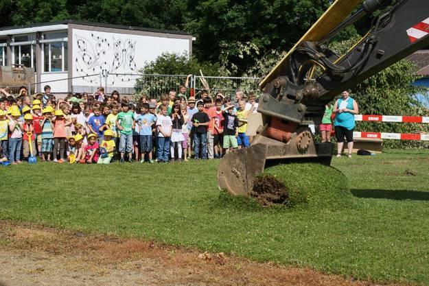 Eine grosse Schaufel gräbt das erste Loch an der Schulstrasse 2