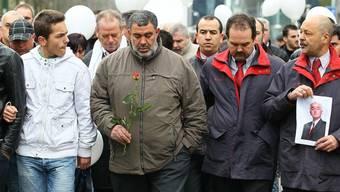 Familienangehörige marschieren zusammen mit Arbeitskollegen des toten Familienvaters in Brüssel