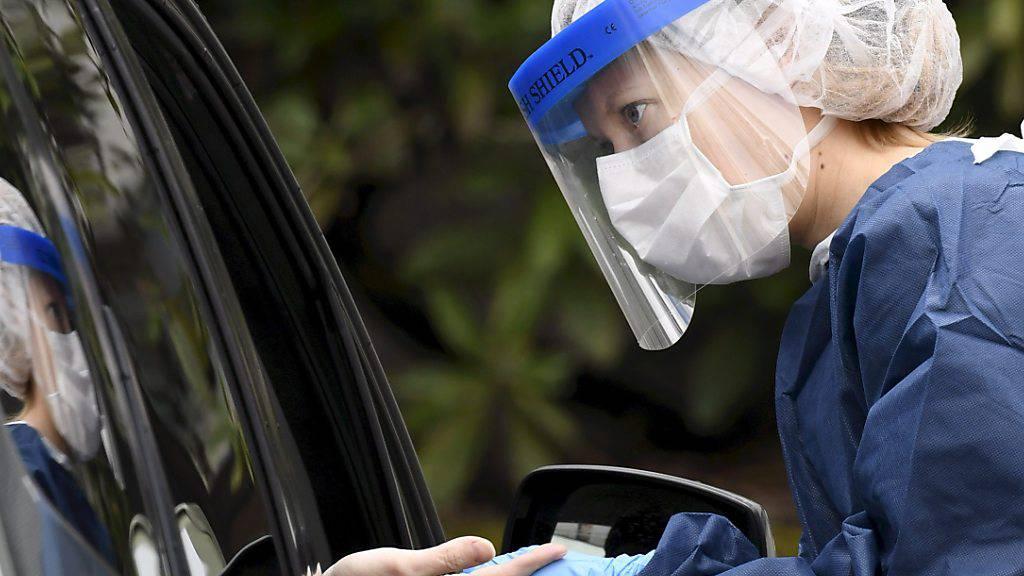 Eine medizinische Mitarbeiterin in Schutzkleidung macht einen Antikörper-Test von einem Patienten an einer Covid-19-Teststation im finnischen Vantaa, bei der die Patienten mit ihrem Auto durchfahren können. Foto: Emmi Korhonen/Lehtikuva/dpa