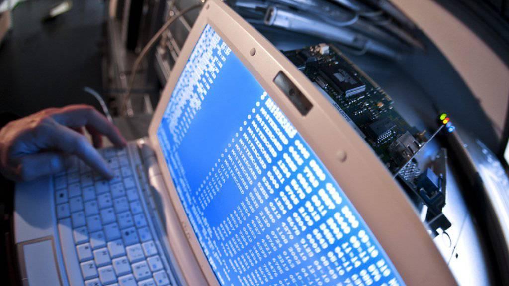 Ein Mann tippt Befehlszeilen in seinen Laptop - im so genannten Darknet können sich Internetnutzer unerkannt bewegen (Symbolbild).