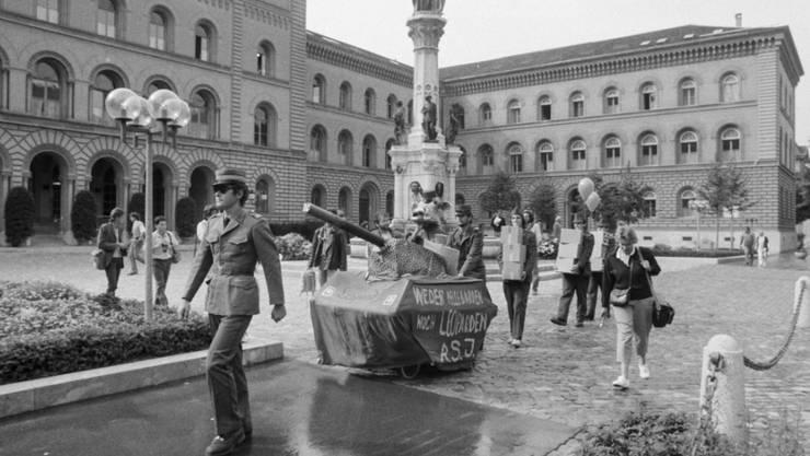 """Am 13. September 1986 werden in der Bundeskanzlei im Bundeshaus in Bern die Unterschriften der Initiative """"Für eine Schweiz ohne Armee und für eine umfassende Friedenspolitik"""" der """"Gruppe für eine Schweiz ohne Armee"""" (GSoA) eingereicht. Dabei fährt sogar ein selbstgebastelter Panzer aus Karton vor."""