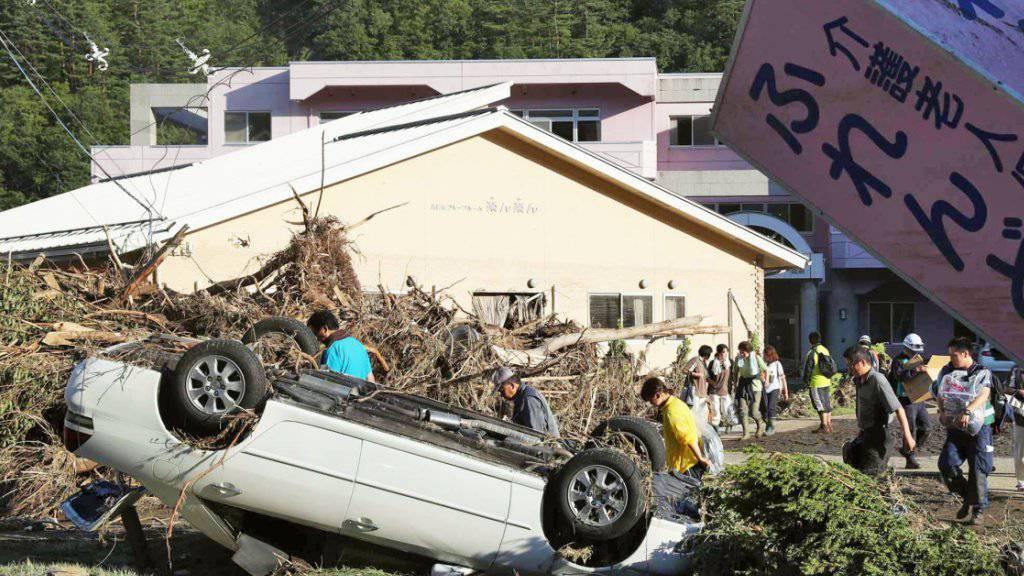 Ein Auto liegt verkehrt herum vor dem Pflegeheim, in dem mehrere Menschen beim Sturm starben.