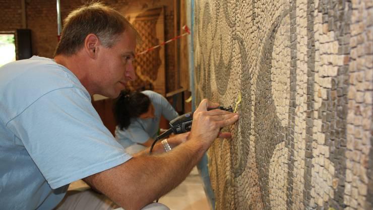 André Zehrfeld und Susanna Sbaraglia verhelfen dem Mosaik, das einst den Säulengang einer römischen Villa zierte, zu neuem Halt.