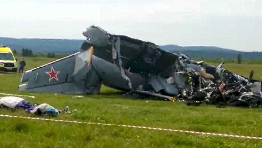 Die Trümmer eines abgestürzten zweimotorigen Flugzeugs vom Typ L-410 liegen innerhalb eines abgesperrten Bereichs.