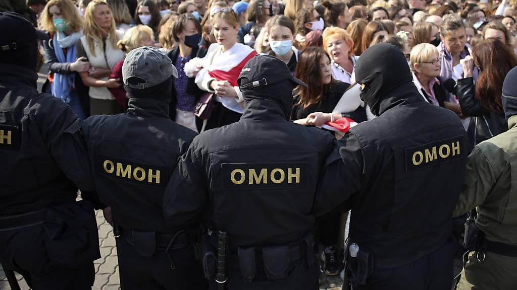 Polizisten der Spezialeinheit OMON stehen bei einem Protest gegen die Ergebnisse der belarussischen Präsidentenwahl vor den Demonstrantinnen. Foto: -/Tut.by via AP/dpa