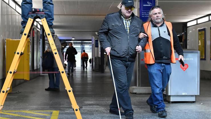 Der sehbehinderte Thomas Biedermann wird von einem SBB-Mitarbeiter um eine Leiter herumgeführt, die in der Martin-Disteli-Unterführung im Weg steht.