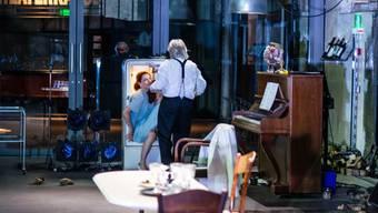 """Der Kellner (Urs Bihler) befreit die junge Frau (Larissa Keat) aus dem Kühlschrank. """"Nachspielzeit"""" von Jan Sobrie hatte am 12. Juni 2018 im Zürcher Schiffbau Uraufführung."""
