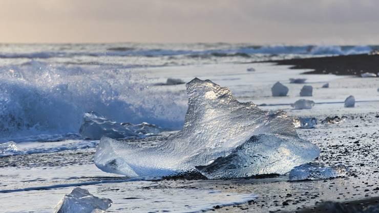 Bizarre Eisbrocken von einem nahen Gletscher, die vom Meer an den Strand gespült wurden. Diamond Beach, Island