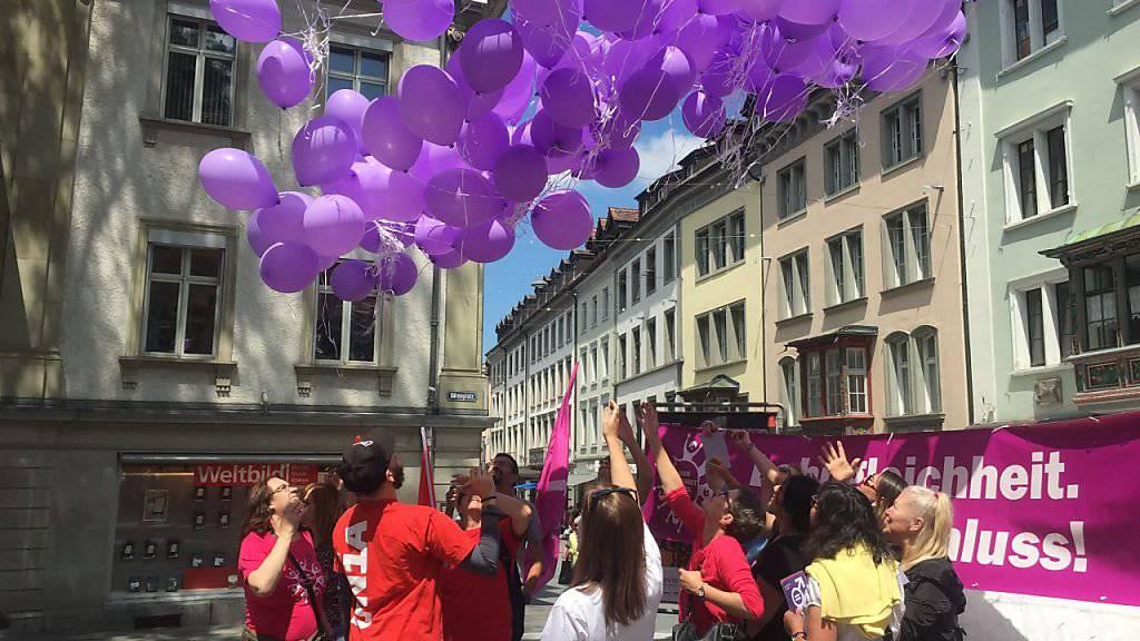 Frauen fordern Lohngleichheit und lassen lila Ballone in den St. Galler Himmel steigen.