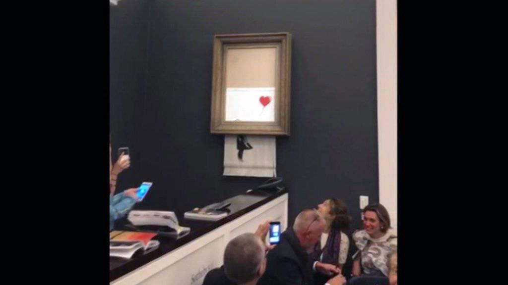 """Das Bild """"Girl with Balloon"""" des englischen Streetart-Künstlers Banksy wurde unmittelbar nach der Auktion von einem von ihm im Rahmen eingebauten Schredder zerstört. (Archivbild)"""