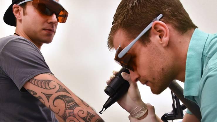 Silas Müller lässt sich von Jan Bolliger ein Tattoo weglasern.