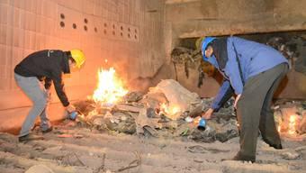 Matthias Grütter von der Aargauischen Gebäudeversicherung (links) und Erich Widmer von der Basler Versicherung entfachten gemeinsam das Feuer in der Kehrichtverbrennungsanlage . msl