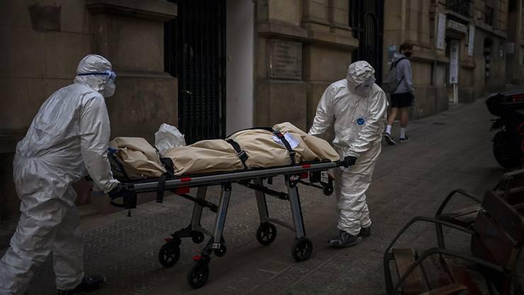 dpatopbilder - Leichenbestatter transportieren den Leichnam eines älteren Menschen, der in einem Pflegeheim an Covid-19 gestorben ist. Foto: Emilio Morenatti/AP/dpa