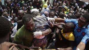Aus den Trümmern des eingestürzten dreistöckigen Gebäudes in Lagos wird ein Kind geborgen. (AP Photo/Sunday Alamba)