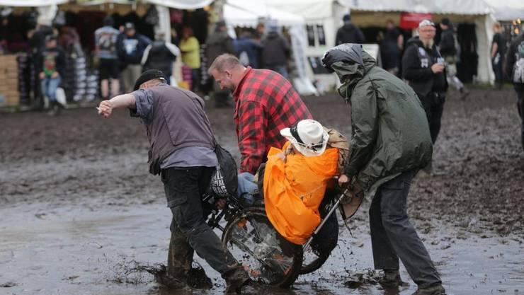 Besucher des Wacken Open Air bugsieren einen Rollstuhl durch den Morast.