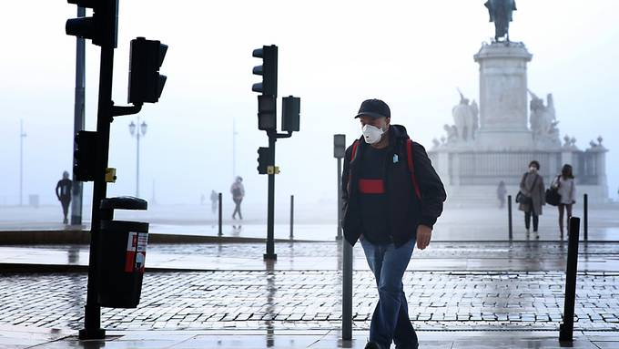 Ein Mann mit Mund-Nasen-Schutz geht durch Lissabon. Foto: Pedro Fiuza/ZUMA Wire/dpa