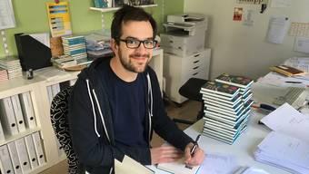 Kilian Ziegler signiert seine Kolumnensammlung «Vorübergehend stehen bleiben», die im Knapp-Verlag erscheint.