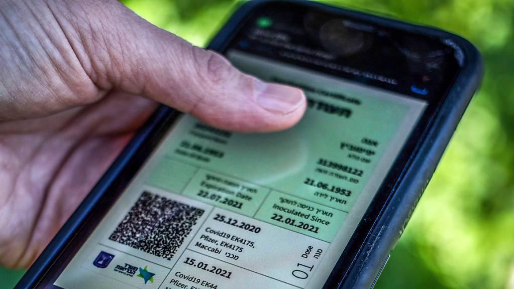 Ein Mann hält ein Smartphone in der Hand, auf dem der sogenannte «Grüne Pass» abgebildet ist. Wegen steigender Corona-Infektionszahlen gilt in Israel seit Donnerstag wieder der sogenannte Grüne Pass.